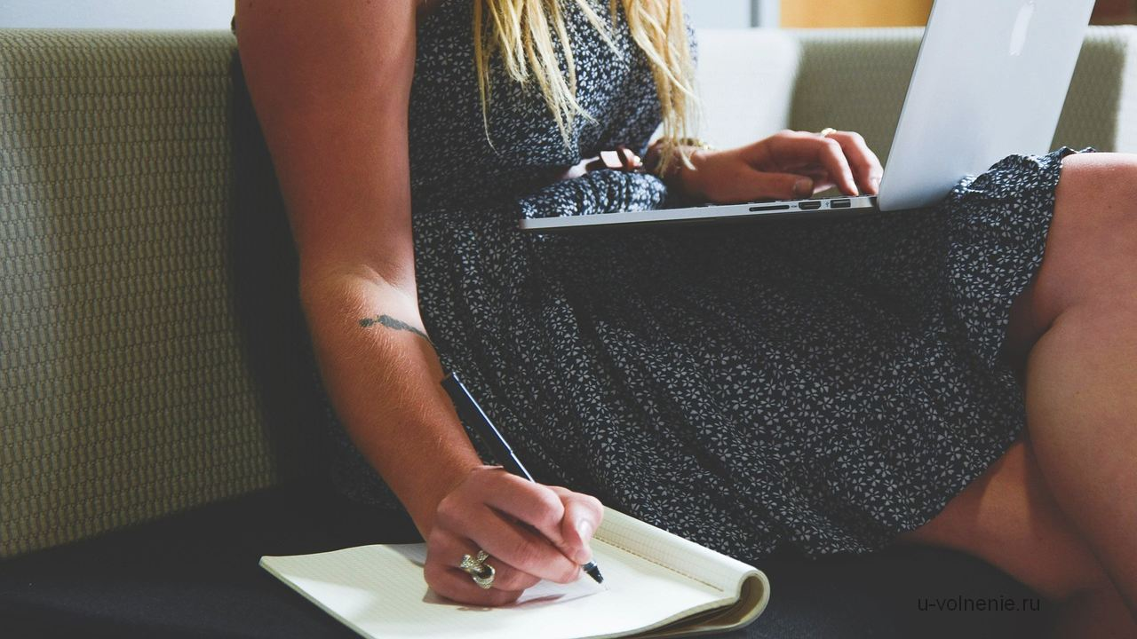 девушка с ноутбуком на коленях пишет ручкой