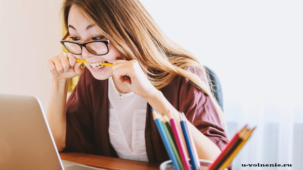 девушка возле ноутбука грызет карандаш