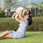 мама подкидывает ребенка на природе