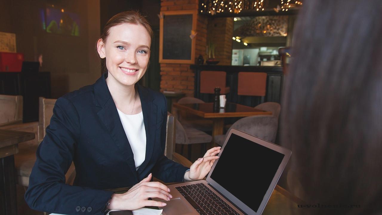 девушка одна сидит за ноутбуком и улыбается