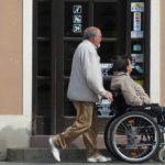 мужчина везет женщину в инвалидном кресле